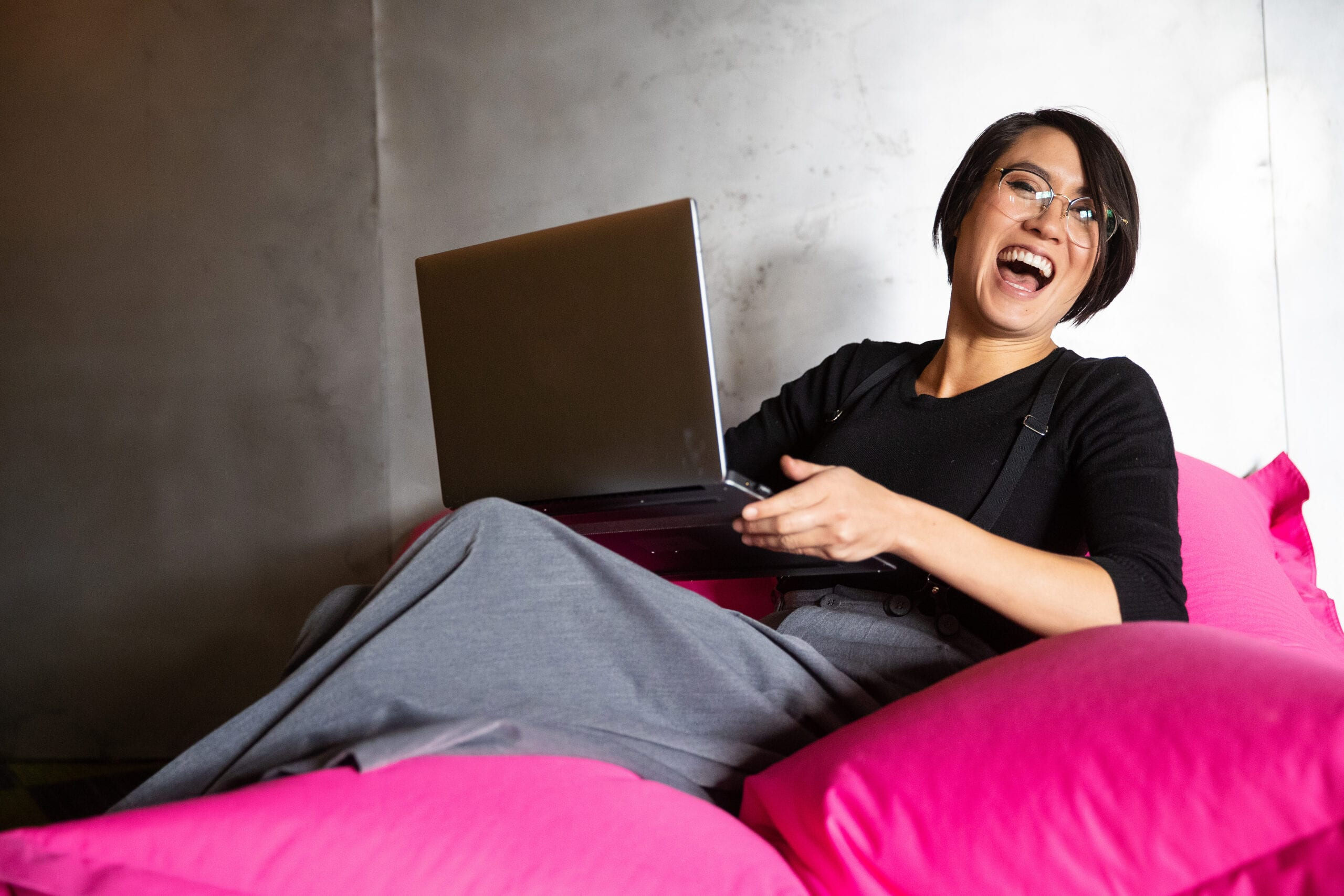 Pretty Asian woman working on laptop while sitting on beanbag chair in office